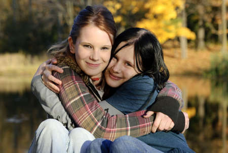 Two cute Caucasian sisters hug each other on a beautiful autumn day Stock Photo