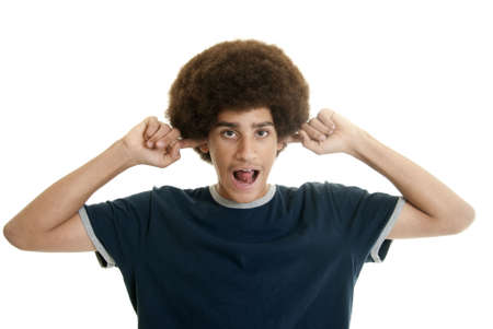 rebelling: Mixed-race teenage boy with her fingers in his ears making noises Stock Photo