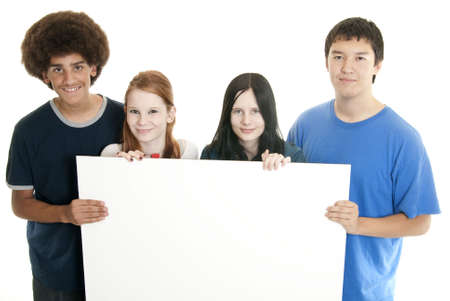 Four teenagers of various ethnic backgrounds holding a blank sign.