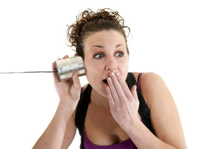 Attractive Caucasian woman listening to a string telephone with a surprised expression. Stock Photo - 6163202