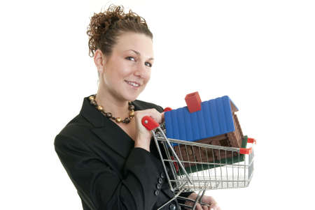 Attractive Caucasian woman holding miniature shopping cart with a house in it. Stock Photo - 6163194