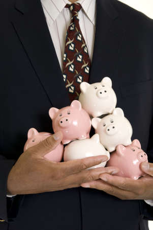 African American businessman holding a pile of piggy banks isolated on white. Shallow DOF. Focus on hands. photo