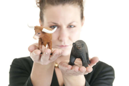 Attractive Caucasian female holding a bull and bear symbolizing the stock market. Shallow DOF. Focus on bull. Stock Photo - 6264061