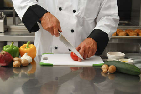 cutting boards: A chef cutting fresh vegetables in a restaurant kitchen.