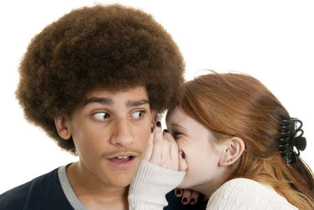 A young Caucasian girl whispers a secret to a mixed-race teen boy photo