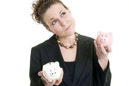 Attractive Caucasian female holding a white and a pink piggy bank making a decision. Stock Photo - 6351560