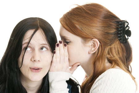 confide: A teenage Caucasian girl whispers a secret to her sister. Focus on face of dark haired girl.