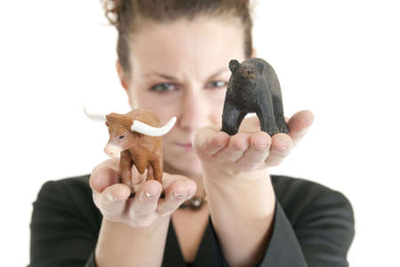 Attractive Caucasian female holding a bull and bear symbolizing the stock market. Shallow DOF. Focus on bull, bear and fingertips. Stock Photo - 6384855