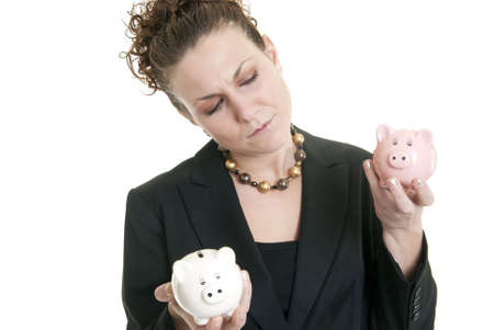 Attractive Caucasian female holding a white and a pink piggy bank making a decision. Stock Photo - 6474878