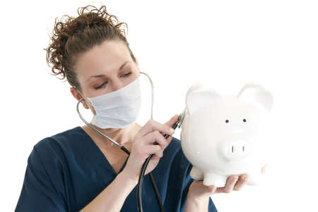 Beautiful, smiling Caucasian nurse listening to a piggy bank with a stethoscope photo