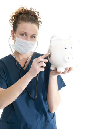 Beautiful Caucasian nurse listening to a piggy bank with a stethoscope photo