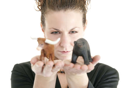 Attractive Caucasian female holding a bull and bear symbolizing the stock market. Shallow DOF. Focus on face. Stock Photo - 6727085