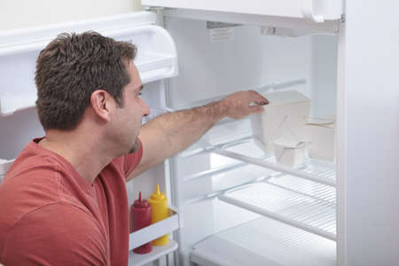 Attractive Caucasian male reaching into a sparse refrigerator photo