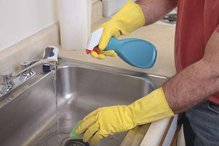 d�sinfectant: Caucase m�le avec des gants de capsule nettoie le dissipateur