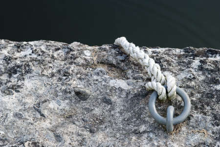 a rope tied to a ring anchored in stone