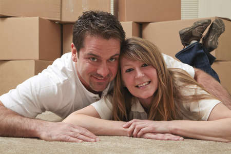 Attractive Caucasian couple lying on the floor in front of boxes in an empty house