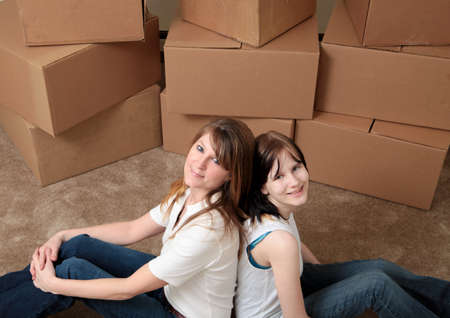 Mother and daughter sit back to back while taking a break from moving photo
