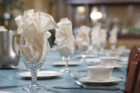 bue: Napkins, silverware, stoneware and glasses on a banquet table. Focus on first glass with napkin. Stock Photo