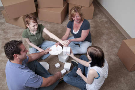 A family sits on the floor sharing Chinese food with boxes in the background photo
