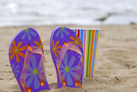 Flip flops and a colorful cup on a beach in the sun. Stock Photo
