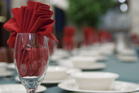 stoneware: Napkins, silverware, stoneware and glasses on a banquet table. Focus on first glass with napkin. Stock Photo