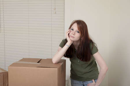 Teenage girl with a bored expression leaning on moving boxes. photo