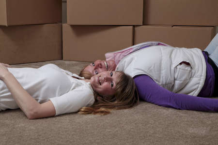 roommates: Female roommates lying on the floor in front of moving boxes. Stock Photo