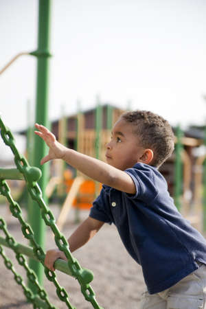 Cute multi-racial boy at the park playing Stock Photo
