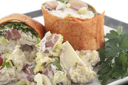 Chicken salad wrap with potato salad. Shallow DOF. Focus on potato salad. Stock Photo