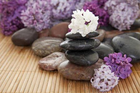 Pile of Rocks mit Blumen auf eine Bambusmatte. Weiße Blume oben auf den Stapel im Mittelpunkt.