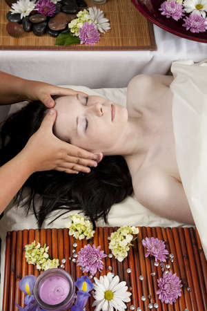 A young Caucasian woman lies on a massage table with a candle and flowers getting her head massaged. photo