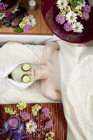 A young Caucasian woman lies on a massage table with a candle and flowers with a face mask on and cucumbers. photo