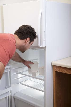 fridge: Attractive Caucasian male reaching into a sparse refrigerator Stock Photo