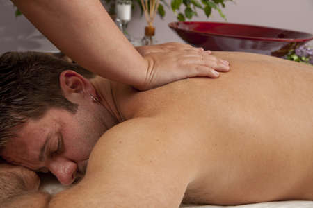 A Caucasian man lies on a massage table getting a massage. photo