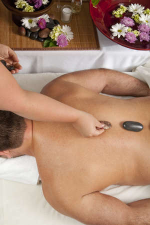 A Caucasian man lies on a massage table getting hot stones put on his back photo