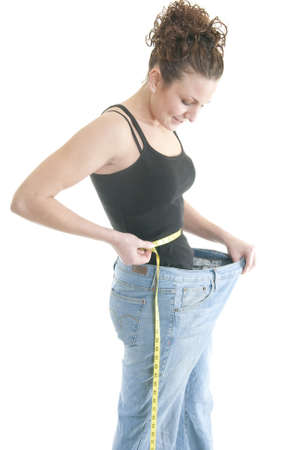 A Caucasian woman measures her waist while wearing pants that are too large. photo