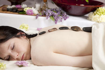 A young Caucasian woman lies on a massage table with hot stones on her back. photo