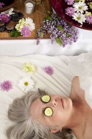 A Caucasian woman lies on a massage table with cucumber on her eyes.