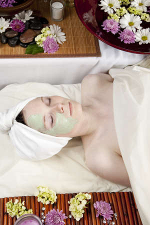 A young Caucasian woman lies on a massage table with a candle and flowers with half of her face covered in a face mask. photo