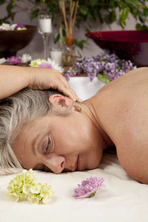 A Caucasian woman lies on a massage table getting a massage. Stock Photo