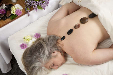 A Caucasian woman lies on a massage table with stones on her back.