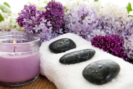 pampering: Three rocks on a white towel with flowers on a bamboo mat. Focus on third rock. Shallow DOF. Stock Photo