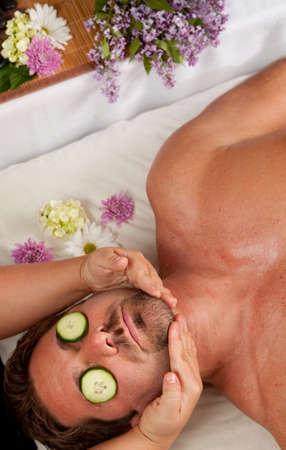 cucumbers: A Caucasian man lies on a massage table getting a massage with cucumbers on his eyes.