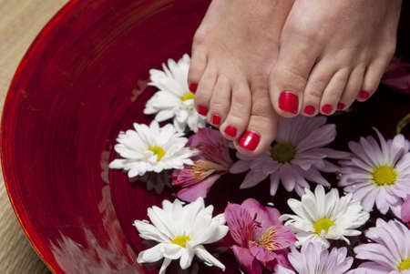 A women with red nail polish on her toes holds her feet above a bowl of water and flowers.