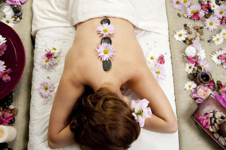 A young woman at a spa waiting for a massage with hot stones and flowers on her back.