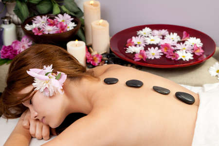 stones with flower: A young woman at a spa waiting for a massage with hot stones on her back.