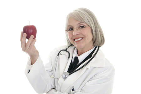 A mature female doctor wearing a stethoscope holds an apple. photo