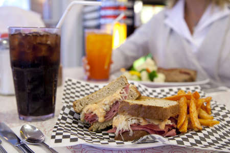 reuben: A Reuben sandwich with sweet-potato fries rests on a table across from an out-of-focus woman.
