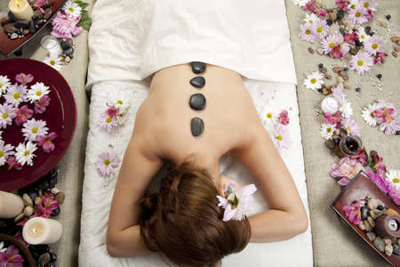 hot stone massage: A young Caucasian woman lies on a massage table with hot stones on her back and candles and flowers surrounding her.