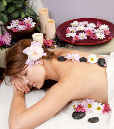 massage face: A young Caucasian woman lies on a massage table with hot stones on her back and candles and flowers surrounding her.